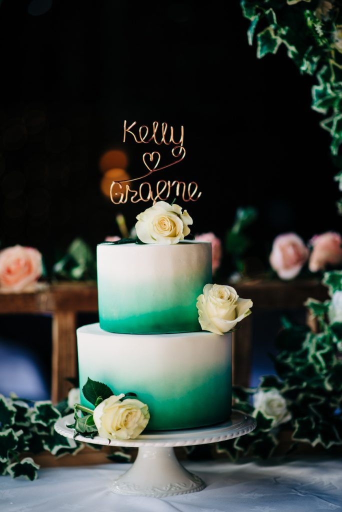 Green and white wedding cake with roses