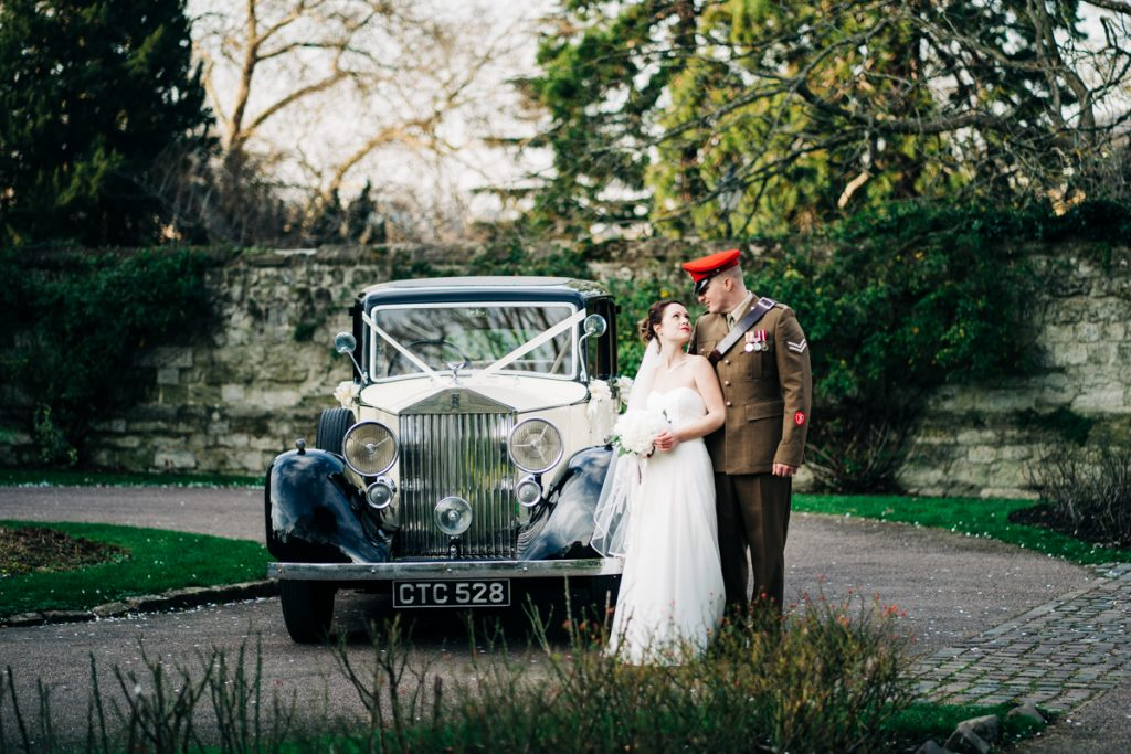 bride and groom with a rolls royce military wedding
