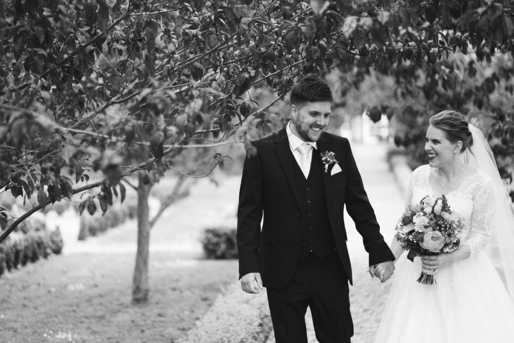 newly married couple walk at secret gardens