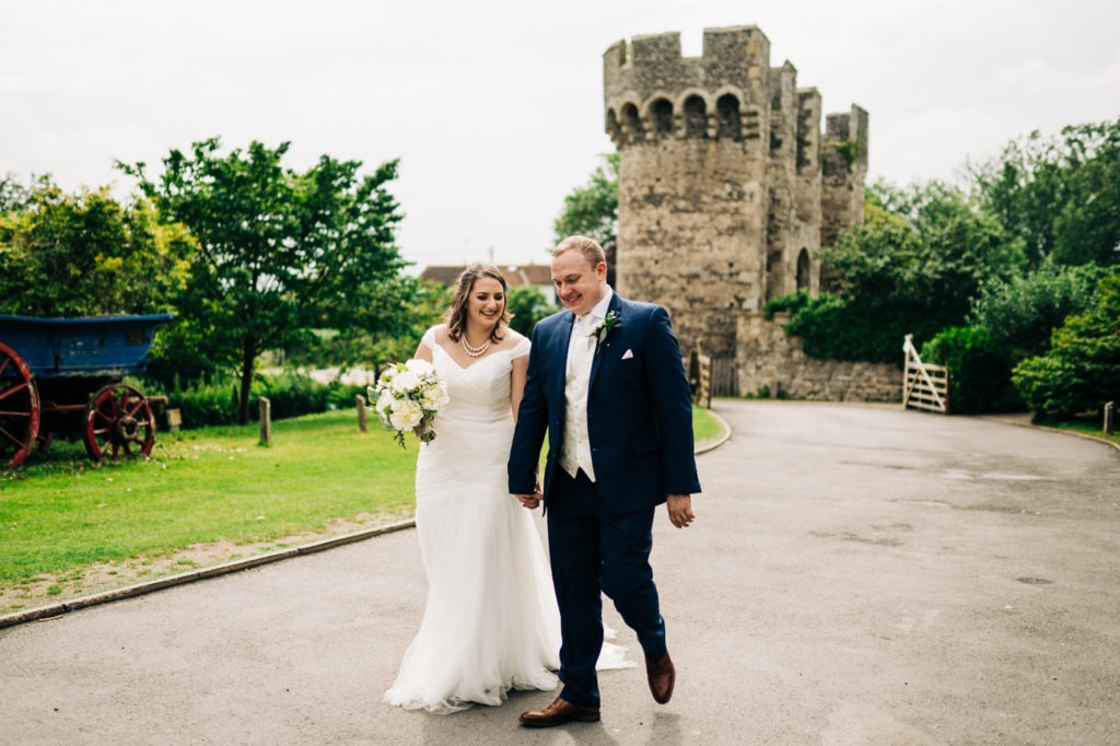 couple walk at cooling castle barn wedding 2019