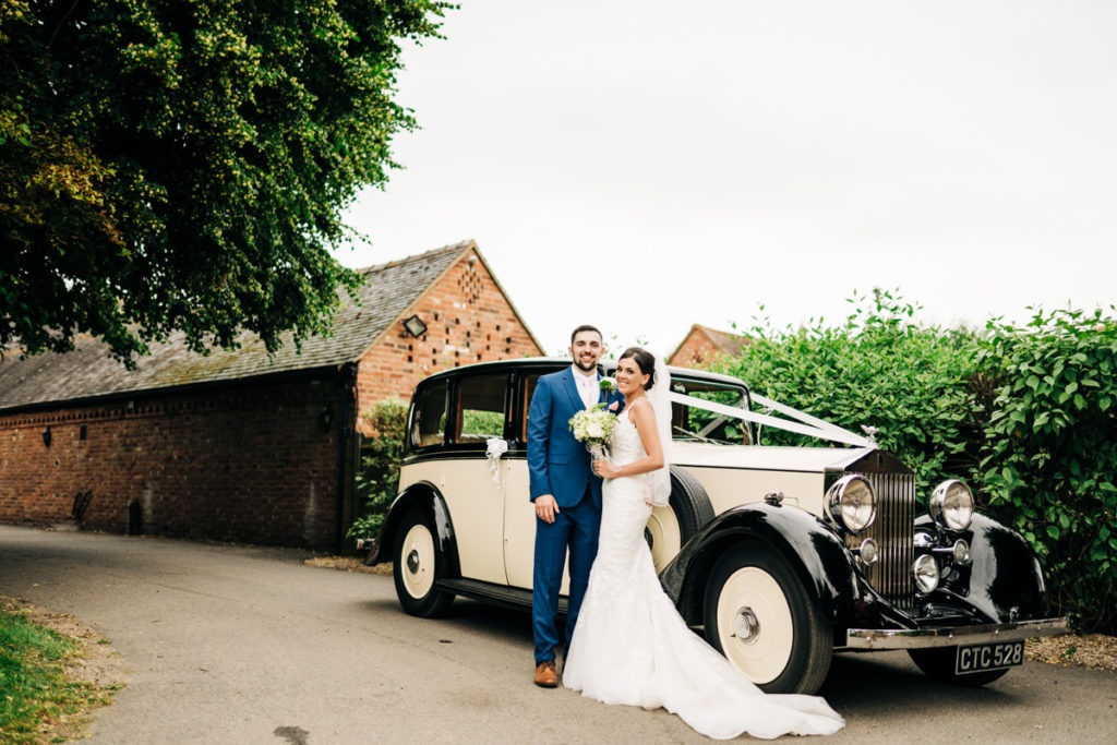 Bride and groom by Rolls Royce upchurch the barnyard