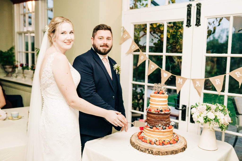 cutting the cake at secret garden wedding