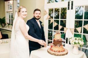 cutting the cake at secret garden wedding