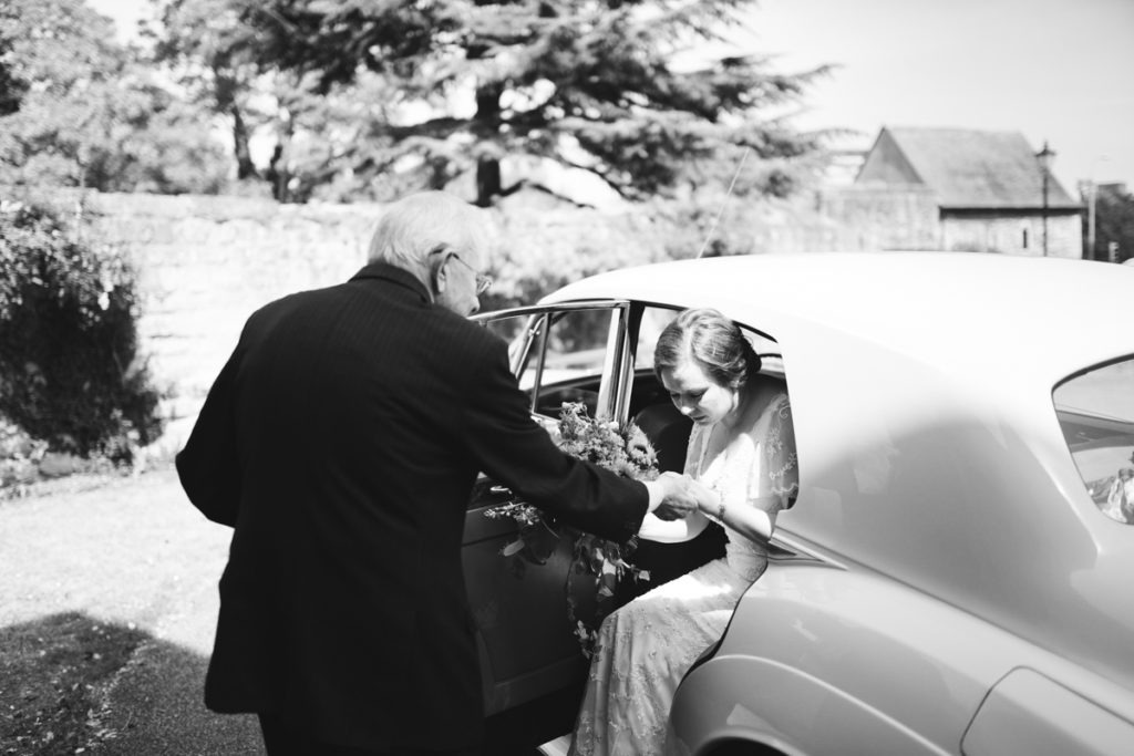 bride being helped out of car by Dad