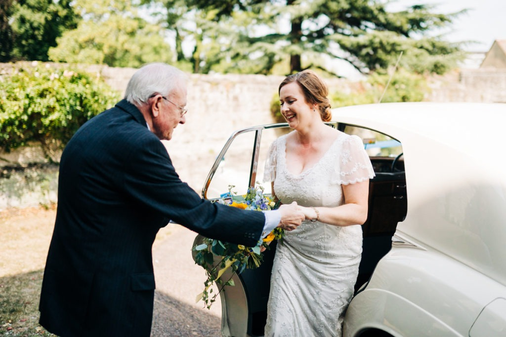 dad helping bride out of car at archbishops palace